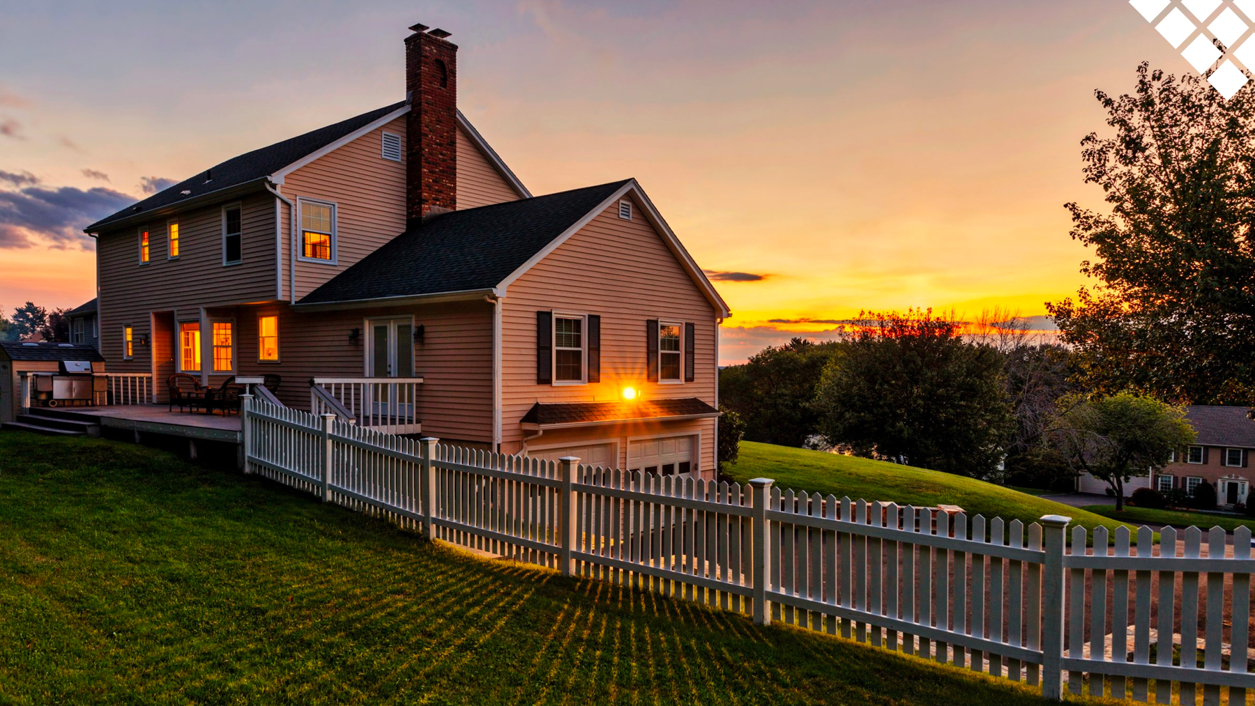 Sunsetting on landscape of home with porch, chimney and picket fence on beautiful green lawn