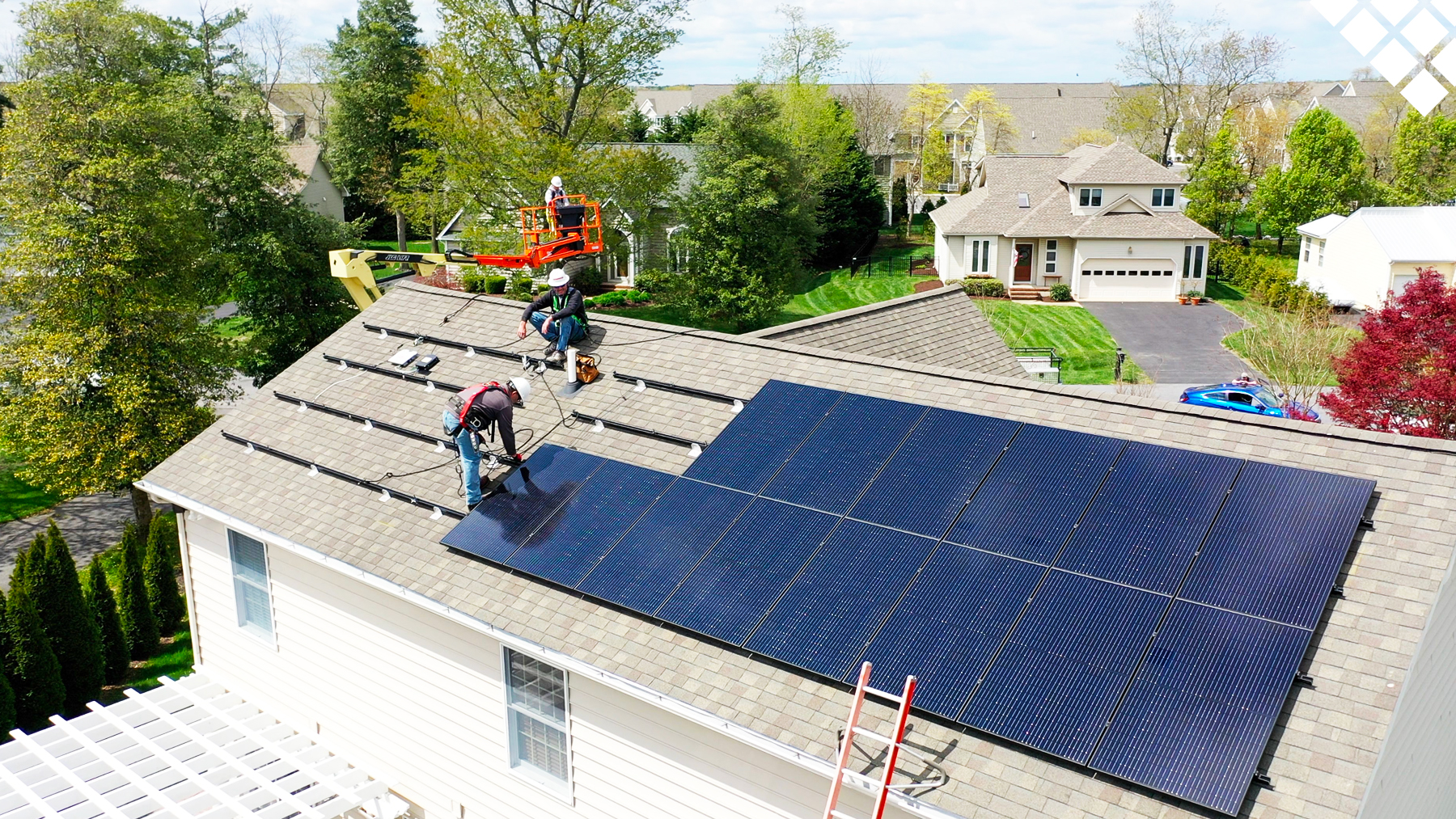 Workers installing solar panels on residential roof in neighborhood