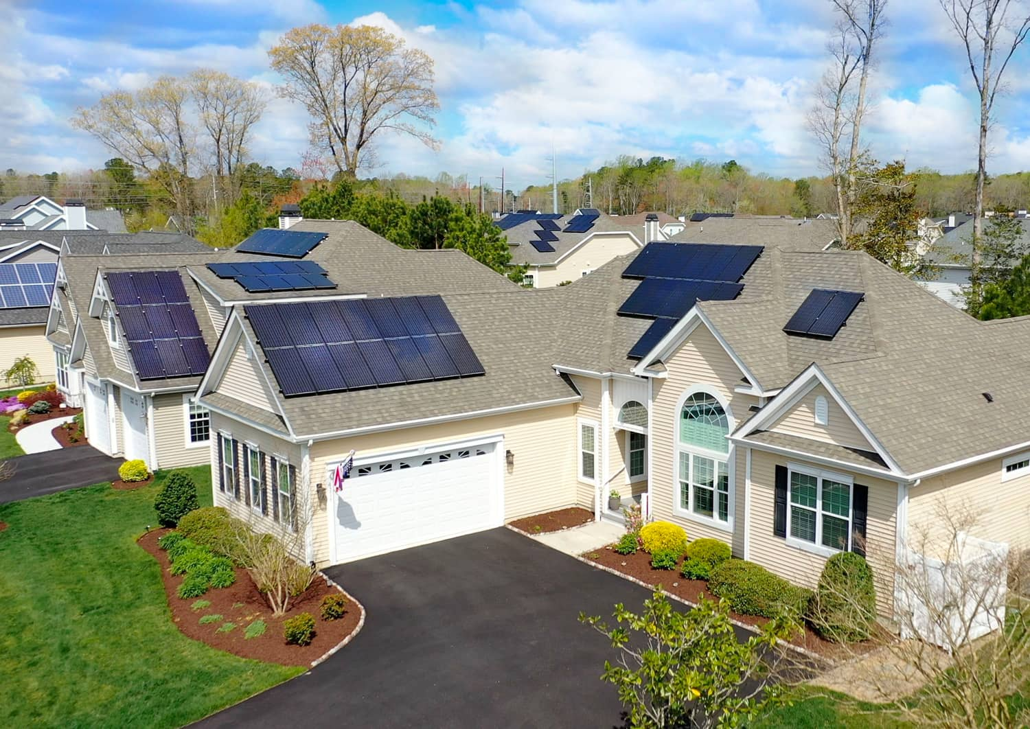 Overhead view of neighborhood and house with solar panels on roof