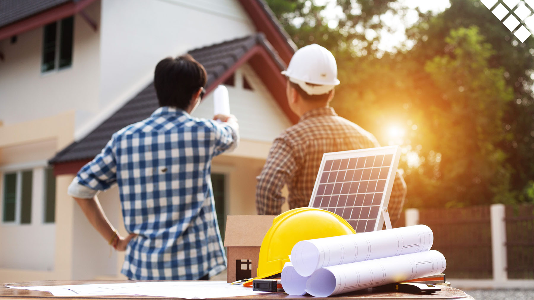 two men reviewing the roof of a home with a solar panel, blue prints, and a hard hat on the table in front of them